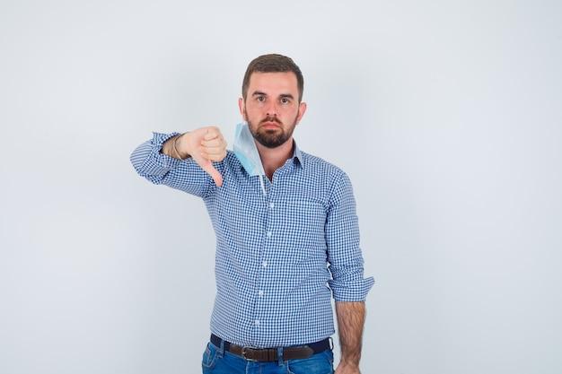 Hombre guapo en camisa, jeans, máscara quitándose la máscara, mostrando el pulgar hacia abajo y mirando disgustado, vista frontal.