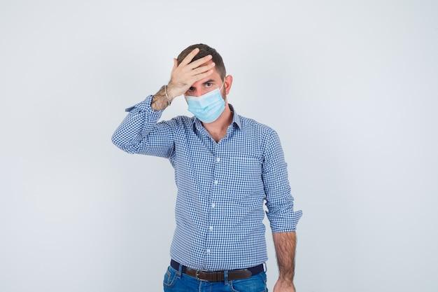 Hombre guapo en camisa, jeans, máscara sosteniendo la mano en la cabeza, con dolor de cabeza y luciendo exhausto, vista frontal.