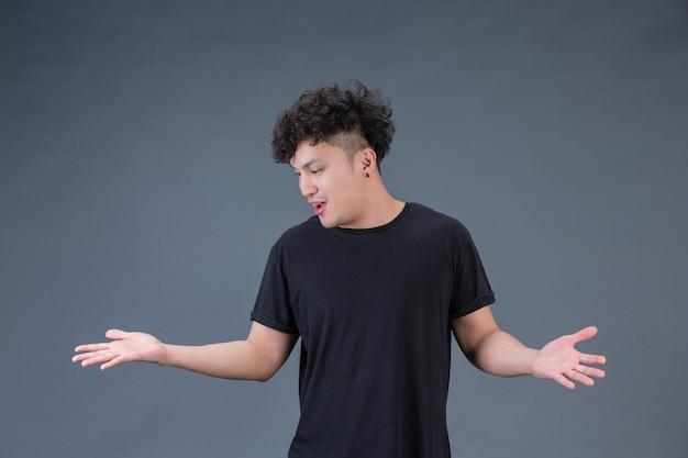 Un hombre guapo con una camisa negra de pie con los brazos
