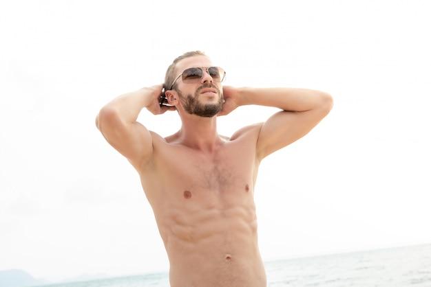 Hombre guapo sin camisa en la playa en verano