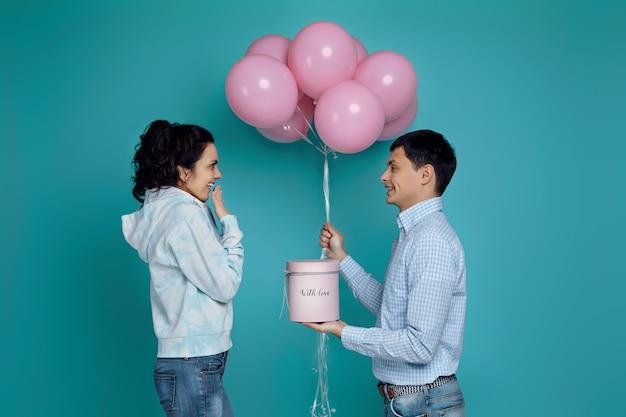 Hombre guapo en camisa presentando caja de regalo y globos rosados a su novia en azul