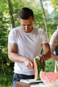 Hombre guapo con camiseta blanca cortando sandía
