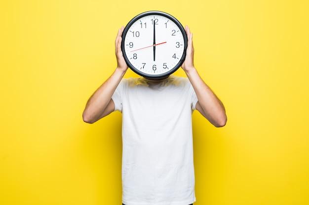 Hombre guapo con camiseta blanca y gafas transparentes sostiene un gran reloj en lugar de su cabeza