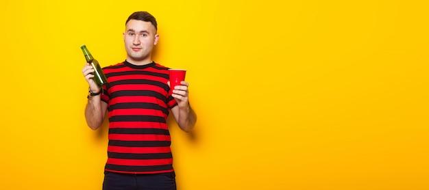 Hombre guapo en camiseta brillante con cerveza