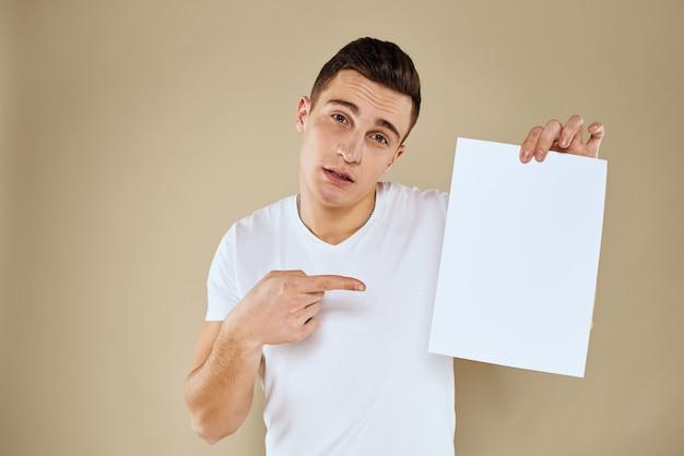 Hombre guapo en una camiseta sostiene una sábana blanca sin una inscripción, espacio libre, espacio vacío, espacio de copia
