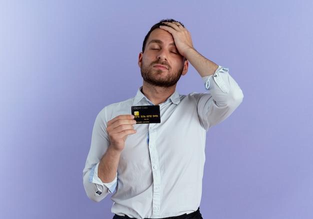 Hombre guapo cansado pone la mano en la frente con tarjeta de crédito aislada en la pared púrpura