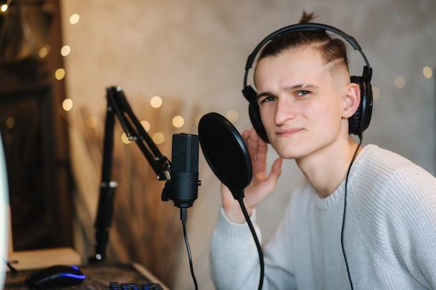 Hombre guapo canta en casa por computadora hombre usa equipo de sonido profesional como micrófono y