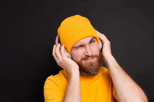Hombre guapo en casual escuchando música con auriculares aislado sobre fondo negro