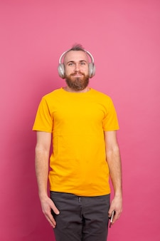 Hombre guapo en casual escuchando música con auriculares aislado sobre fondo rosa