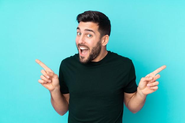 Hombre guapo caucásico aislado en la pared azul que señala el dedo a los laterales y feliz