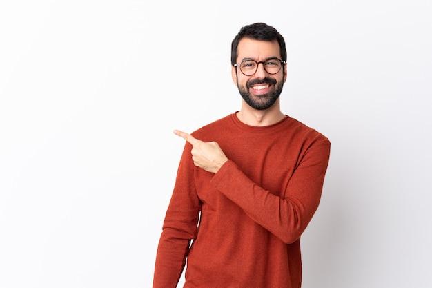 Hombre guapo caucásico con barba sobre pared blanca aislada apuntando hacia un lado para presentar un producto