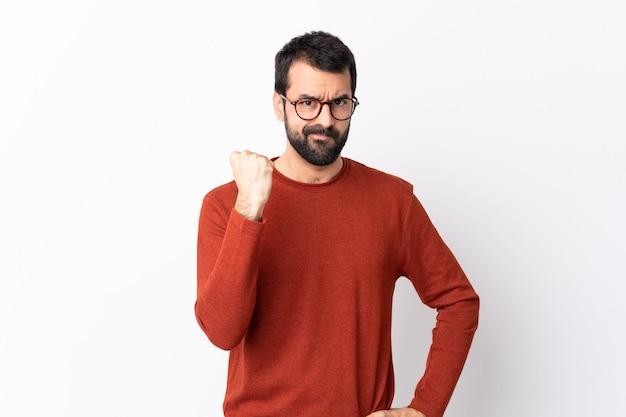 Hombre guapo caucásico con barba sobre pared blanca aislada con gesto enojado