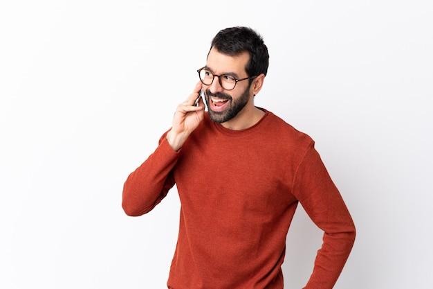 Hombre guapo caucásico con barba sobre pared blanca aislada manteniendo una conversación con el teléfono móvil