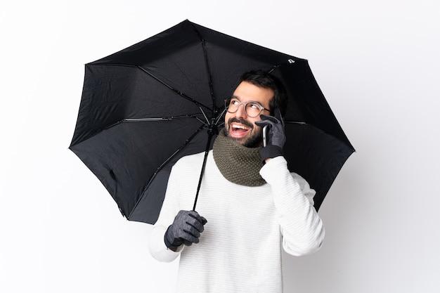 Hombre guapo caucásico con barba sosteniendo un paraguas sobre una pared blanca aislada manteniendo una conversación con el teléfono móvil