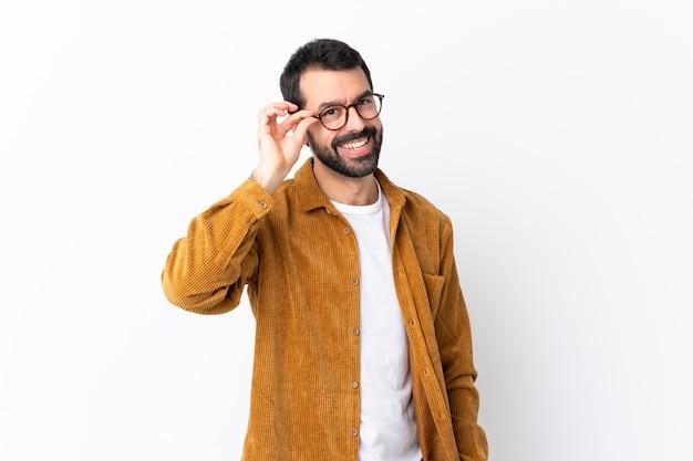 Hombre guapo caucásico con barba vistiendo una chaqueta de pana sobre pared blanca aislada con gafas y feliz