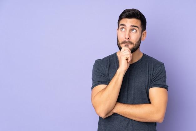Hombre guapo caucásico con dudas y pensando sobre la pared púrpura aislada