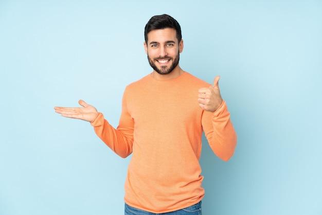Hombre guapo caucásico con espacio en blanco imaginario en la palma y con los pulgares hacia arriba sobre la pared azul