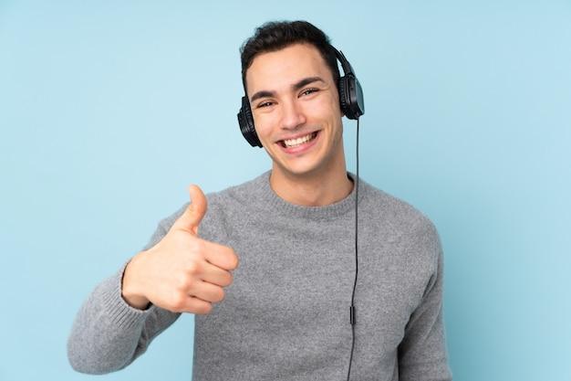 Hombre guapo caucásico joven aislado en la pared azul escuchando música y con el pulgar arriba