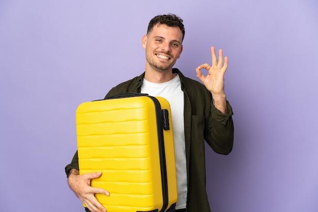 Hombre guapo caucásico joven aislado en la pared blanca en vacaciones con maleta de viaje y haciendo el signo de ok