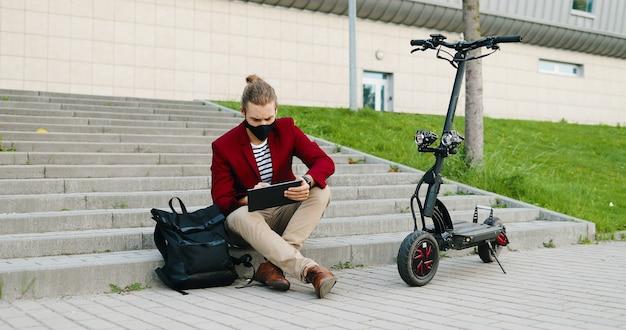 Hombre guapo caucásico joven en máscara y chaqueta roja sentado en pasos al aire libre, trabajando en la computadora de gadget y navegando en línea. chico elegante tocando y desplazándose en el dispositivo de tableta. scooter electrico.