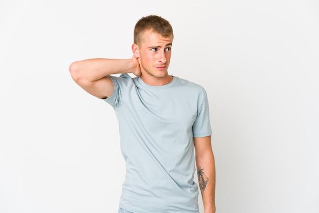 Hombre guapo caucásico joven tocando la parte posterior de la cabeza, pensando y tomando una decisión.