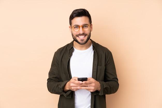 Hombre guapo caucásico en pared beige enviando un mensaje con el teléfono móvil