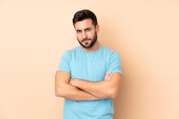 Hombre guapo caucásico en pared beige sintiéndose molesto