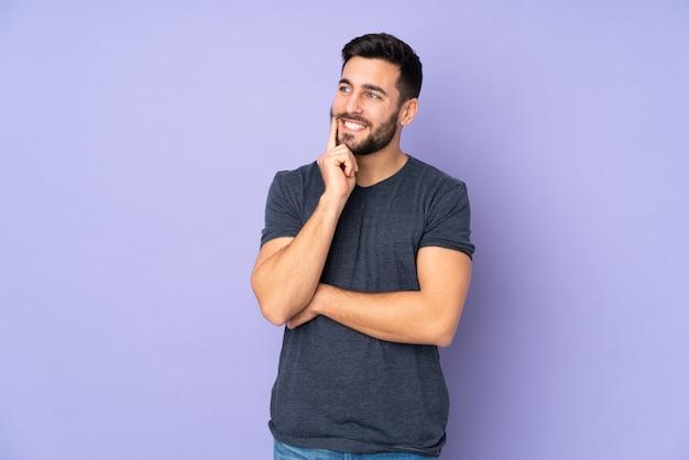 Hombre guapo caucásico pensando una idea mientras mira hacia arriba sobre la pared púrpura aislada