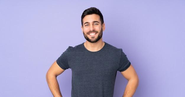 Hombre guapo caucásico posando con los brazos en la cadera y sonriendo sobre pared púrpura aislado