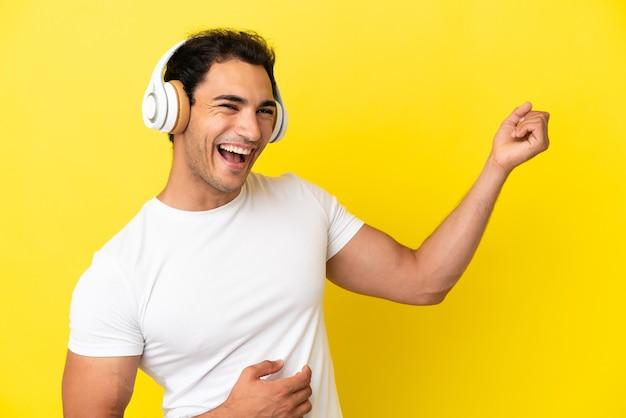 Hombre guapo caucásico sobre fondo amarillo aislado escuchando música y haciendo gesto de guitarra