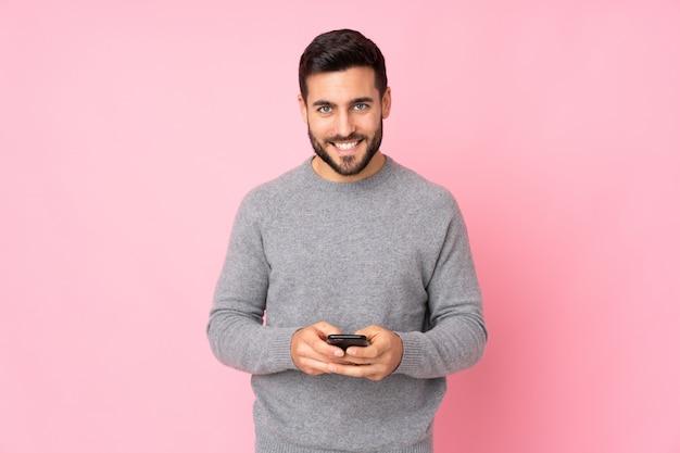 Hombre guapo caucásico sobre pared aislada enviando un mensaje con el móvil