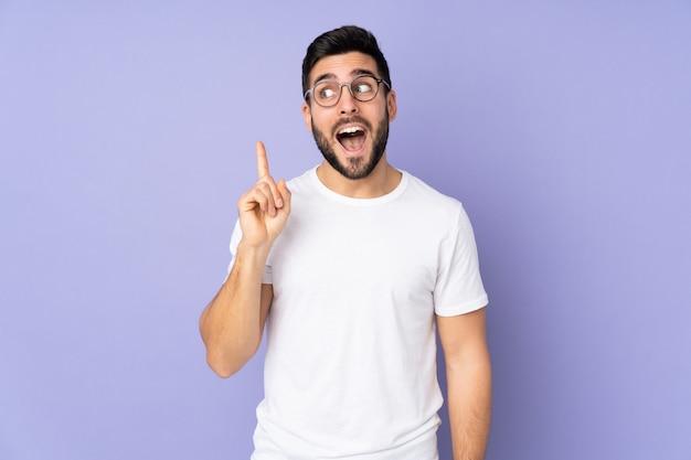 Hombre guapo caucásico sobre pared aislada con la intención de darse cuenta de la solución mientras levanta un dedo