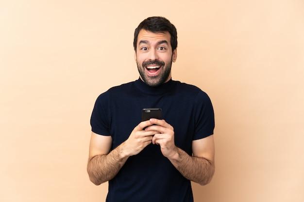 Hombre guapo caucásico sobre pared aislada sorprendido y enviando un mensaje