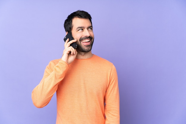 Hombre guapo caucásico sobre pared púrpura aislada manteniendo una conversación con el teléfono móvil