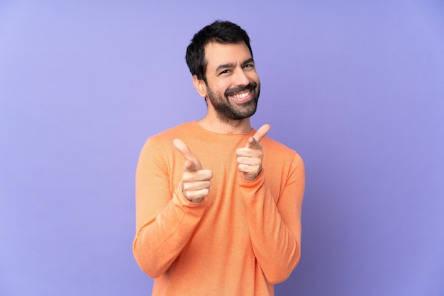 Hombre guapo caucásico sobre pared púrpura aislado apuntando hacia el frente y sonriendo