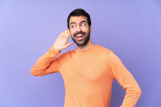 Hombre guapo caucásico sobre púrpura aislado escuchando algo poniendo la mano en la oreja