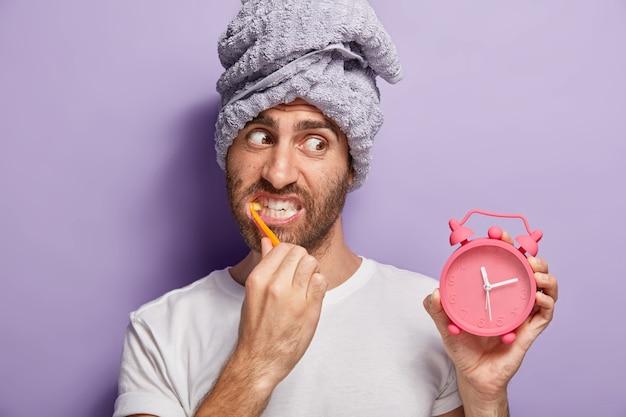 Hombre guapo se cepilla los dientes, se blanquea con pasta de dientes, sostiene el despertador en la mano, se despierta tarde en la mañana, tiene una toalla envuelta en la cabeza, usa una camiseta blanca informal, aislada en la pared púrpura. rutina de la mañana