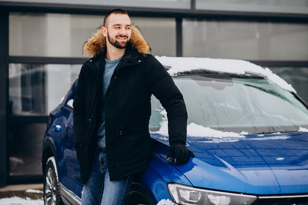Hombre guapo en chaqueta de abrigo de pie en coche cubierto de nieve