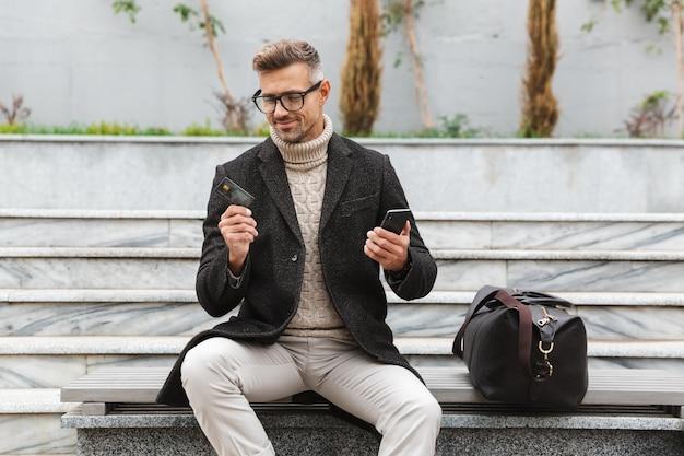 Hombre guapo con chaqueta de compras en línea con teléfono móvil y tarjeta de crédito mientras está sentado al aire libre