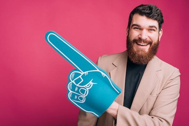 Hombre guapo con chaqueta y un guante de espuma de ventilador azul en rosa.