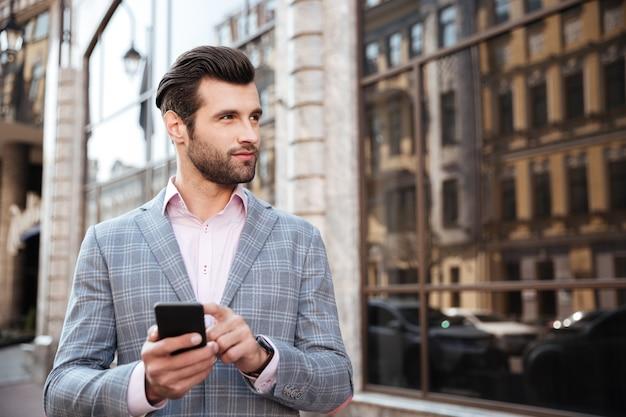 Hombre guapo en una chaqueta de pie y sosteniendo teléfono móvil