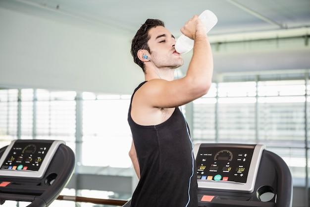 Hombre guapo en cinta rodante bebiendo agua en el gimnasio