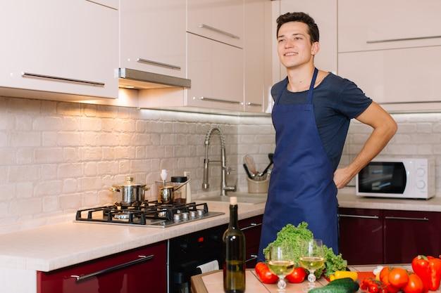 Hombre guapo está cocinando en la cocina y sonriendo
