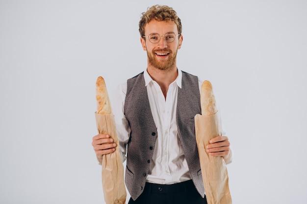 Hombre guapo comiendo baguettes francesas