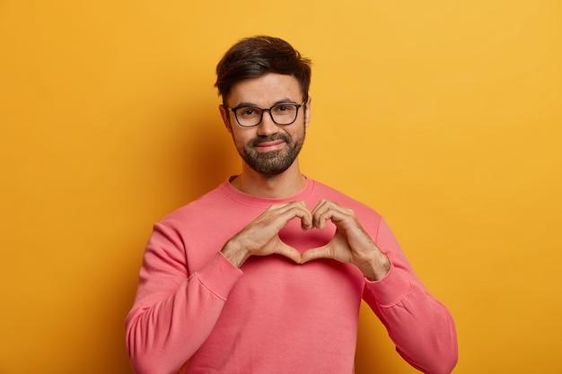 Hombre guapo complacido formas gesto de corazón