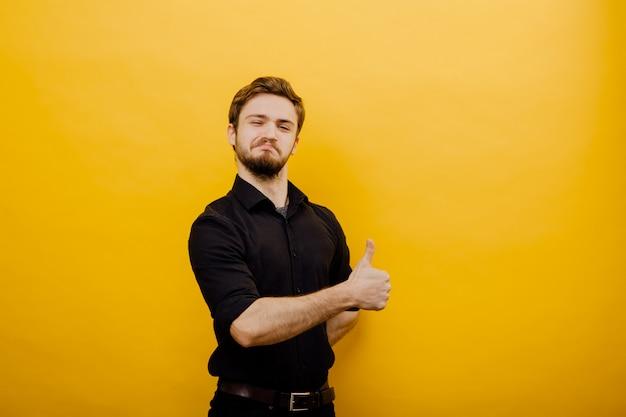 Un hombre guapo complacido, mostrando su pulgar hacia arriba