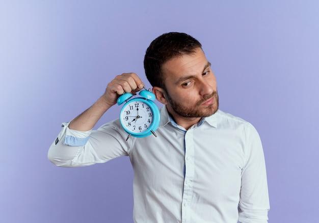 Hombre guapo complacido sostiene el reloj de alarma cerca de la oreja tratando de escuchar aislado en la pared púrpura