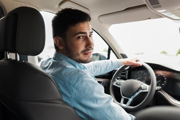 Hombre guapo conduciendo un auto hermoso