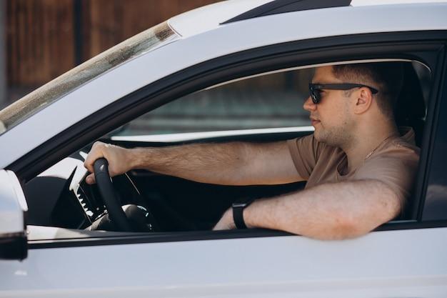 Hombre guapo conduciendo su coche