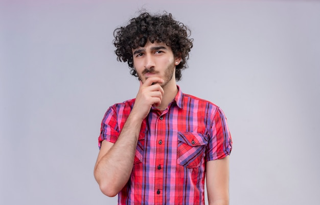 Un hombre guapo confundido con cabello rizado en camisa a cuadros manteniendo la mano en la barbilla